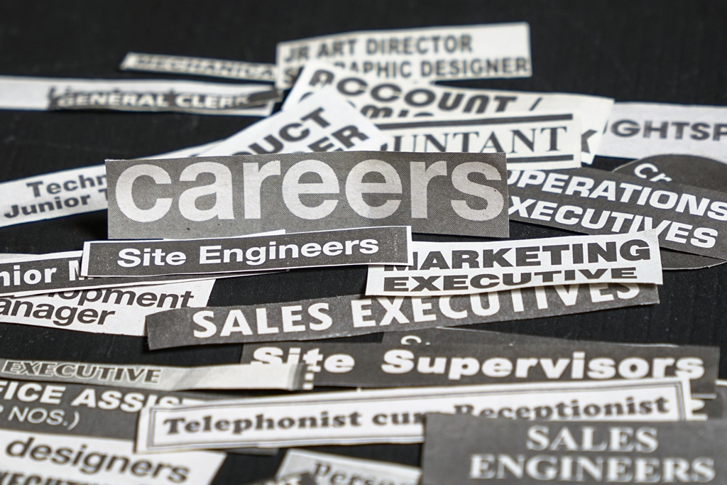 Image showing newspaper cuttings of several job titles in a pile.